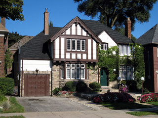 tudor style home with brown trim and ivy