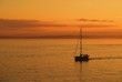 Lone boat sailing in the sunset