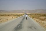 man cycling on sede boker desert road, israel poster