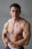 Young Muscular Man Flexing His Biceps poster
