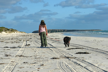 young girl walking dog on lonely beach