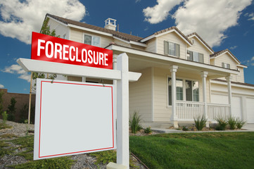 Blank Foreclosure Sign and House with dramatic sky background.