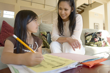 Portrait of a mother helping her daughter with her homework