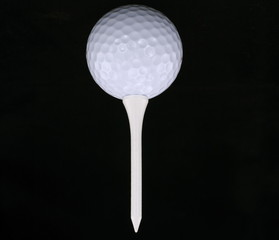 Golf ball  and tee isolated on black