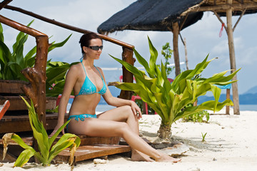 Girl in bikini under tropical hut
