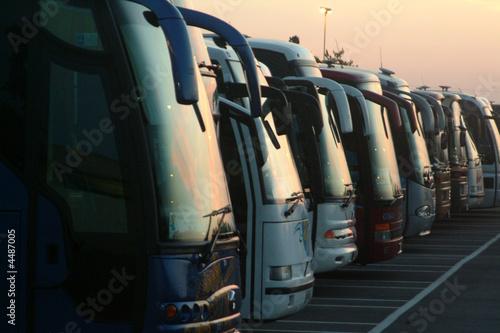 Leinwanddruck Bild Fila di autobus al tramonto