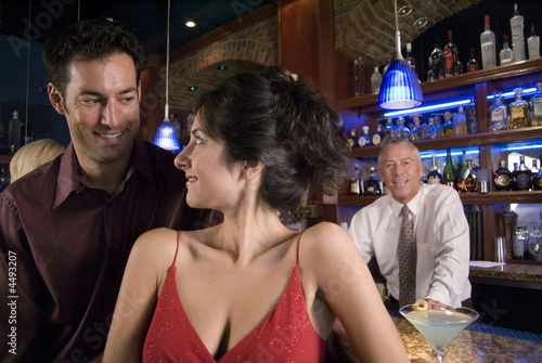 a young couple gets close to each other at a bar