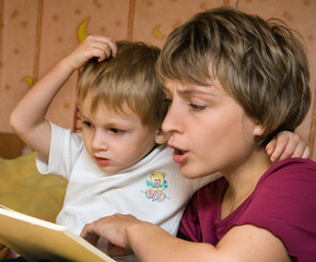 Mother reads the book with the child