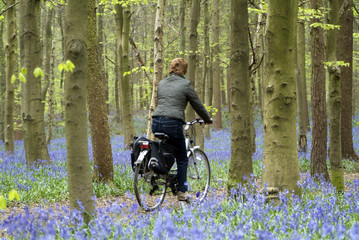 Woman cycling through woods