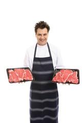 Butcher with trays of T-bone steak