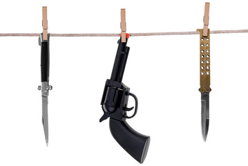 Knifes and toy gun hanging on a clothesline