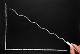 Drawing a declining profit chart on a blackboard.