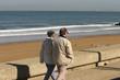 couple de retraités qui marchent en bord de plage