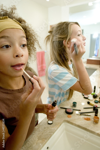 Young girls applying make up Poster