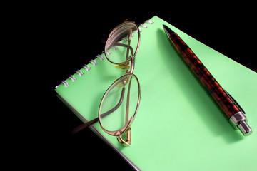 Glasses, pen, notebook