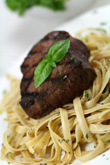 Steak over fettucine with a pesto parmesan sauce