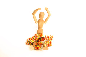 wood person with medical pills isolated in white background