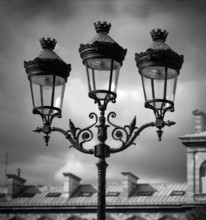 Black and White Image of Lamps Against a Cloudy Sky