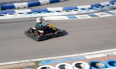 Gokart going fast on open-air circuit.