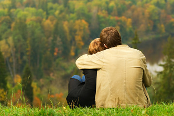 Sweet couple sitting on a hill and looking at the autumn landsca