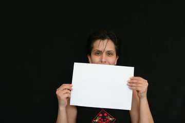girl holding white paper in a black background