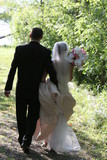 bride and groom in wedding clothes walking poster