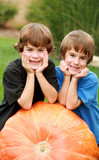 Two Boys Resting on a Pumpkin