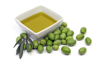 Oilve oil in a square bowl, with some green olives around