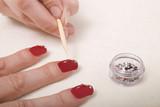 Manicurist applying gems to finger nails poster