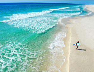 Lone Surfer on Beautiful Deserted Beach