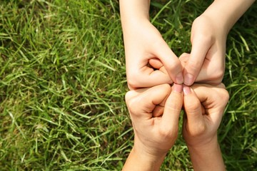 four fists against a grass
