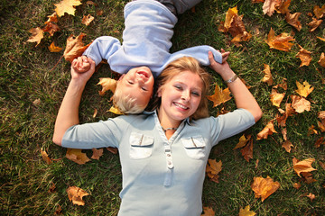 mother and son lied on autumn meadow