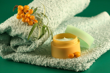 branch of sea-buckthorn berries, a cream and a towel.