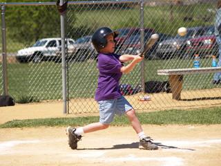 young baseball player hitting baseball