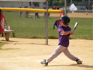 young baseball player after swinging watching ball