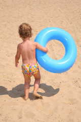 The little girl with a lifebuoy ring goes on sand