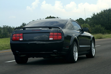 black american muscle car on the road