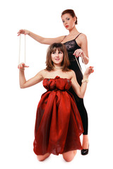 Two beautiful girls acting as wire-puller and marionette