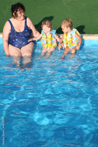 grandma and grandchildren on the side of the pool
