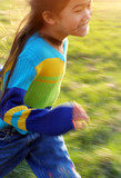 Young girl running on a grassy field, speed blur with sun flare poster