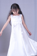 Six years old girl in satin gown playfully twirling around