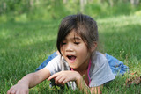 GIrl lying on grass excited about  interesting object in grass poster