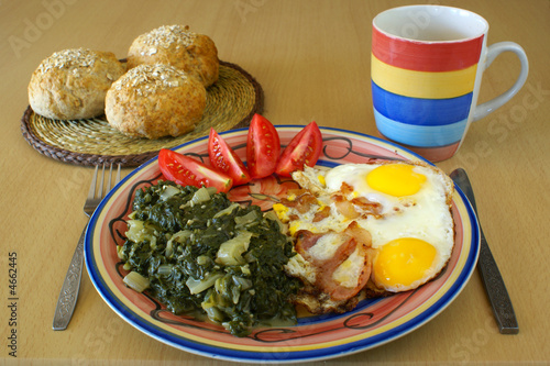 Fried eggs with boiled chard, tomatoes and rolls