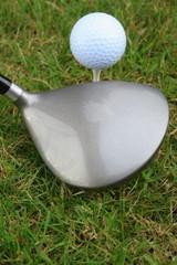 Driver, golf ball, grass and a tee peg