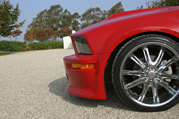 front of red american muscle car with shiny rims