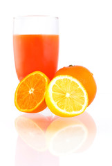 Oranges, piece of lemon and glass of juice