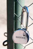 Broken padlock beside open gate
