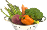 Fresh vegetables with water drops in colander on white isolated