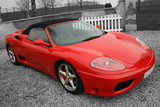 Bright red convertible sports car on a black and white backgroun poster