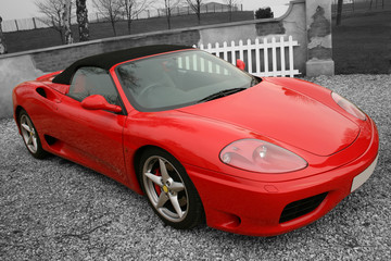 Bright red convertible sports car on a black and white backgroun